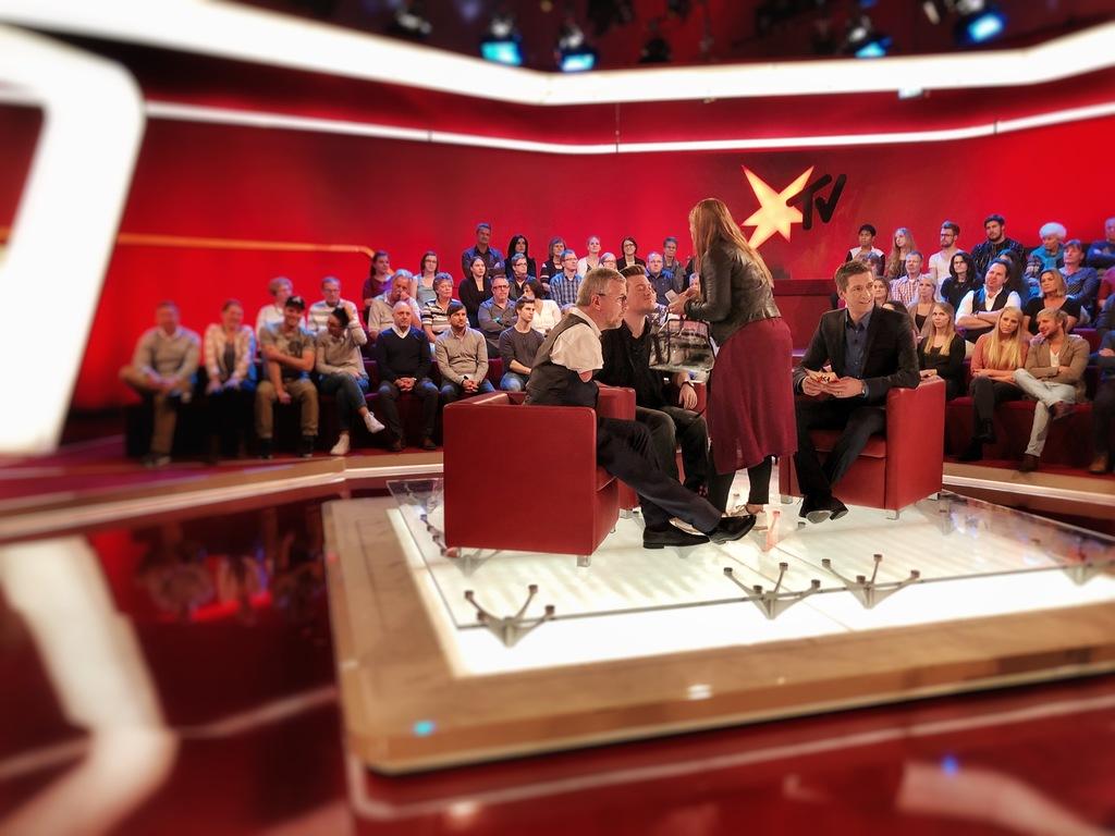 René Schaar im Fernsehstudio von stern TV, während er neben dem Moderator Steffen Hallaschka sitzt und geschminkt wird.