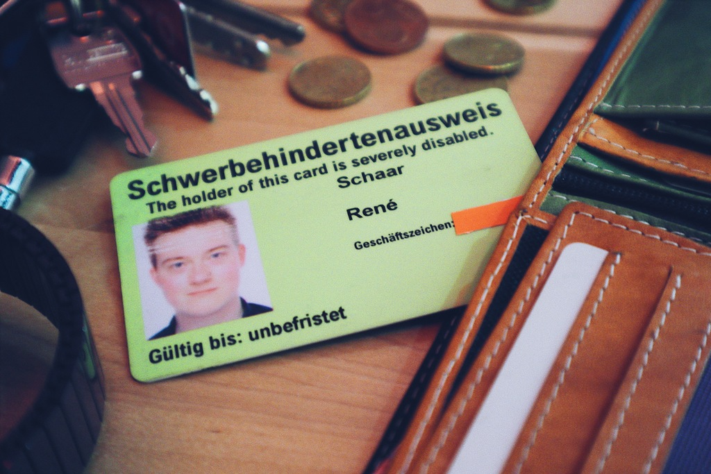 Ein Schwerbehindertenausweis liegt auf dem Tisch neben anderen alltäglichen Dingen wie einem Portemonnaie, Schlüsselbund und Kleingeld.
