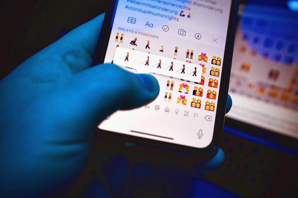 Ein Finger sucht auf einer Smartphone-Tastatur nach neuen Emojis, die Menschen mit Behinderung zeigen.